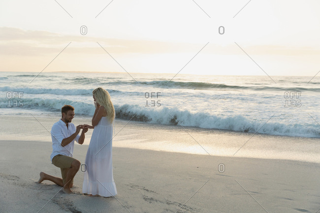 Caucasian man putting ring in woman finger at beach