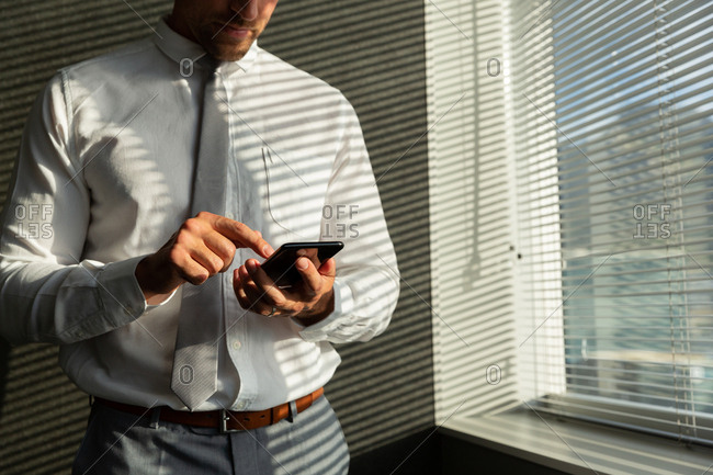 Young Caucasian male executive working on mobile phone while standing near window in a modern office