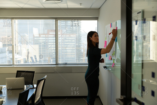 Young female executive writing on sticky notes in a modern office
