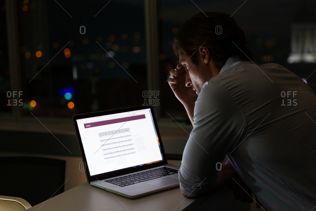Young Caucasian male executive working in laptop at desk in a modern office