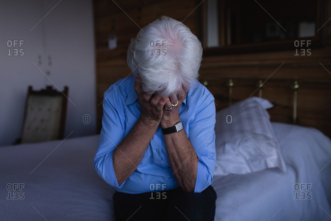 Sad active senior woman covering face with hands while sitting on bed in bedroom at home