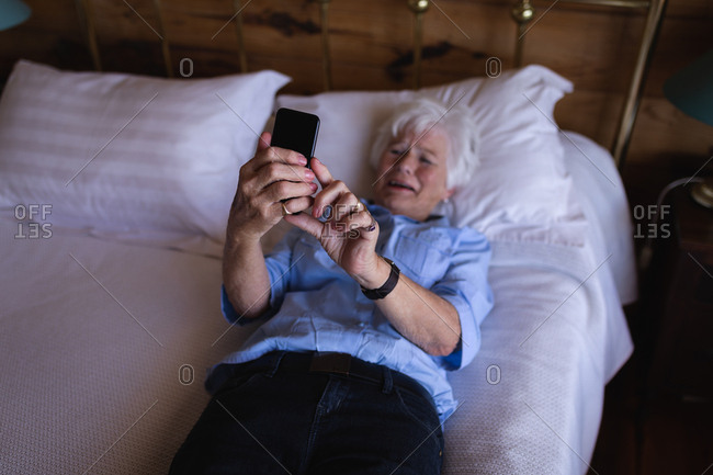 Sad active senior woman using mobile phone while lying on bed in bedroom at home