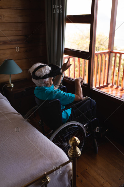Disabled active senior woman using virtual reality head on wheelchair in bedroom at home