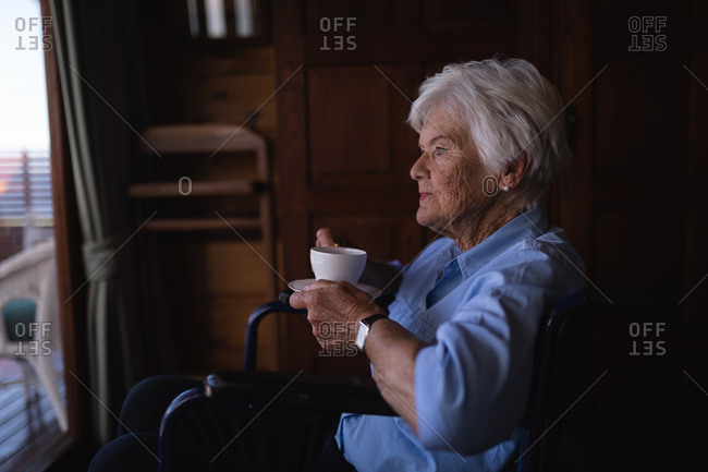 Thoughtful disabled active senior woman with coffee cup sitting on wheelchair in bedroom at home