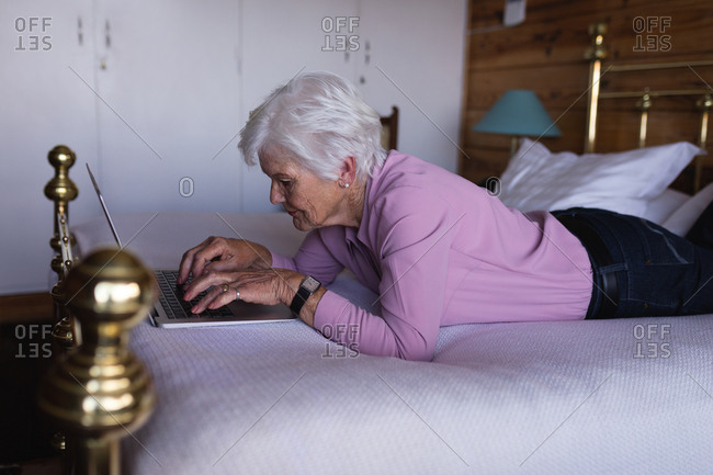 Active senior woman lying on bed and using laptop in bedroom at home