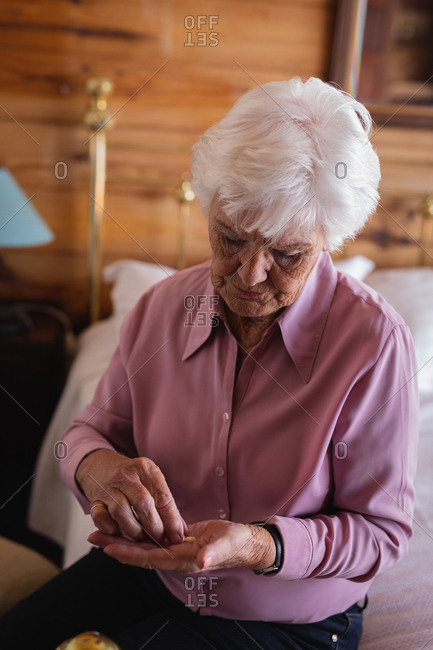 Active senior woman taking medicine in bedroom at home