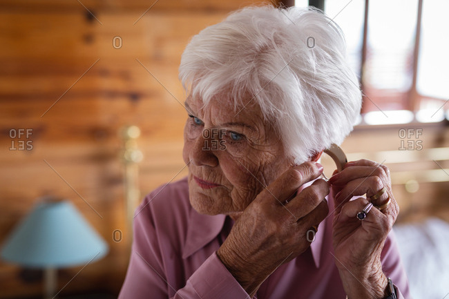 Active senior woman wearing a hearing aid in her ear in bedroom at home
