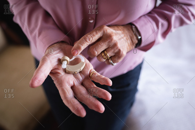 Active senior woman holding hearing aid in hand at home