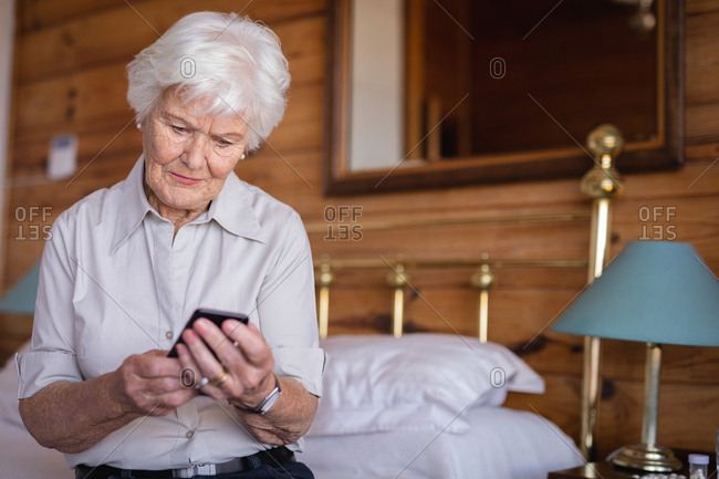 Active senior woman sitting on bed and using mobile phone in bedroom at home