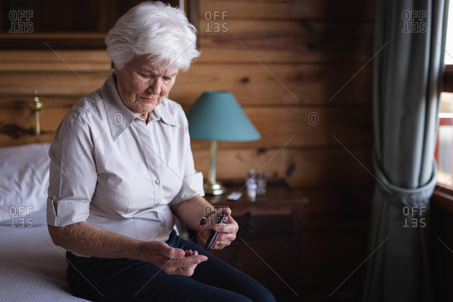 Active senior woman with glucometer checking blood sugar level on bed in bedroom at home