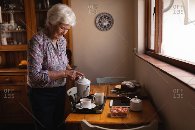 Active senior woman pouring coffee in a cup at dining table in kitchen at home