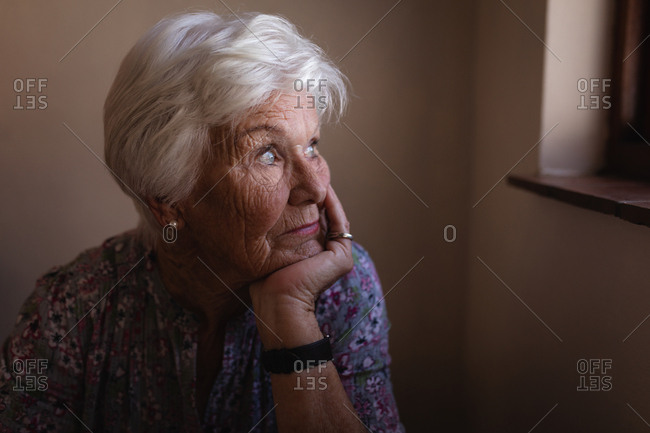 Thoughtful active senior woman with hand on chin looking through window in kitchen at home