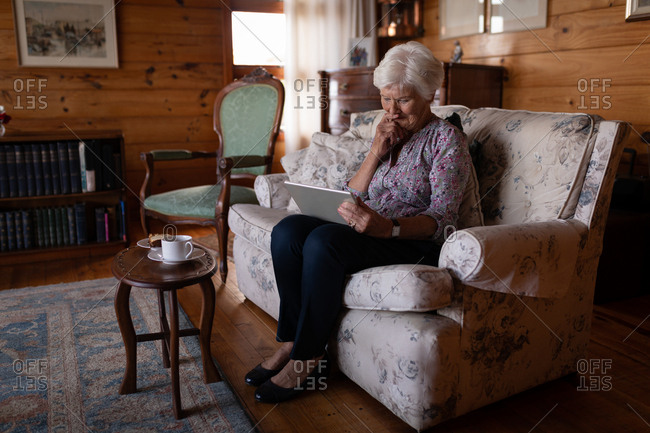 Active senior woman with hand on chin using digital tablet on the sofa at home