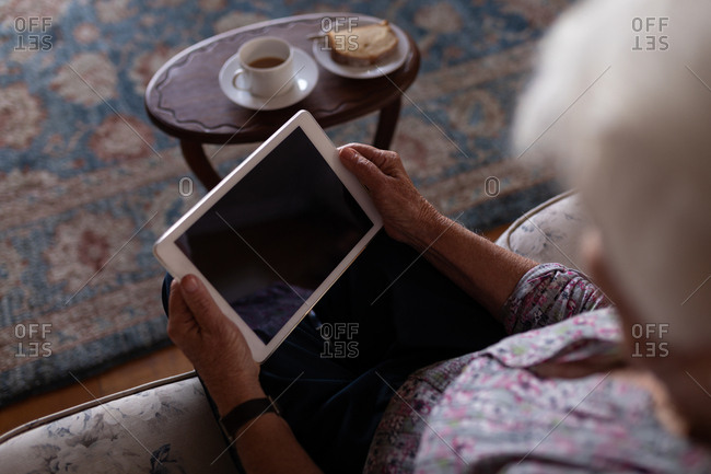 Active senior woman using digital tablet while sitting on the sofa at home