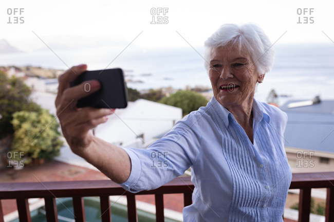 Happy active senior woman taking selfie with mobile phone while standing in balcony at home