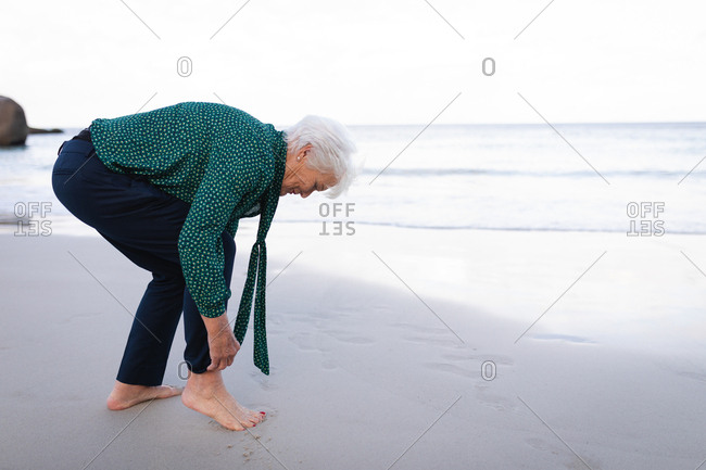 Active senior woman rolling up pant sleeves on the beach
