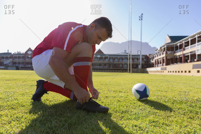 Male rugby player tying shoelaces on the rugby ground