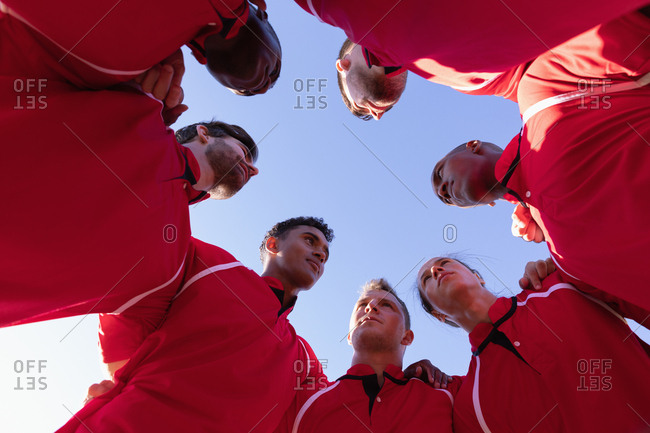 Team of male rugby players forming huddles in the rugby ground