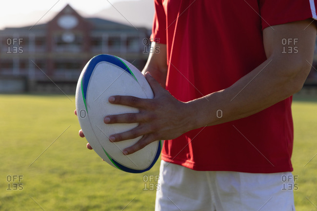 Male rugby player holding rugby ball  in the ground