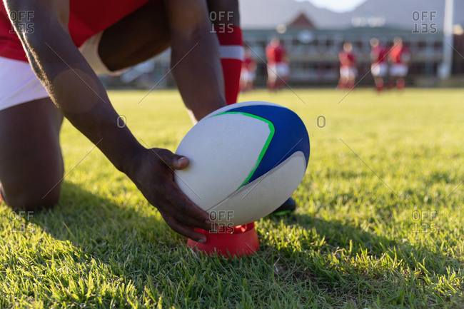 Male rugby player placing rugby ball on a stand in the rugby playground