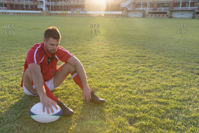 Male rugby player sitting with rugby ball in the ground