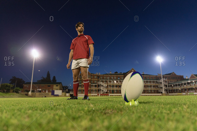 Male rugby player standing with rugby ball in the stadium