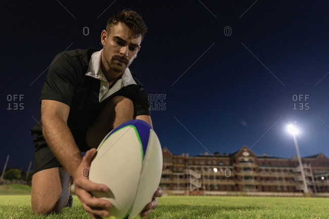 Male rugby player placing rugby ball on a stand in the stadium