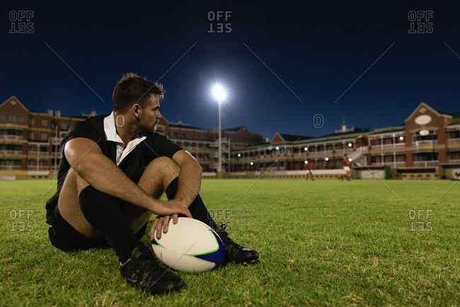 Male rugby player sitting with rugby ball in the stadium