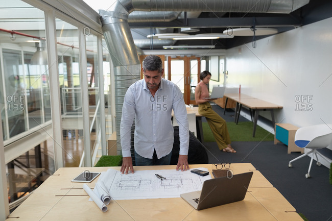 Man working at blueprint at desk in office