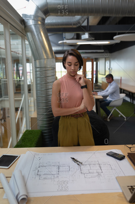 Businesswoman standing and looking at a blueprint at desk in office