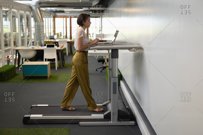 Businesswoman working on laptop while doing exercise on treadmill