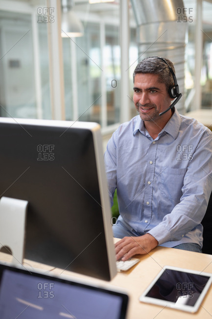 Businessman operating with computer and headset at desk in office