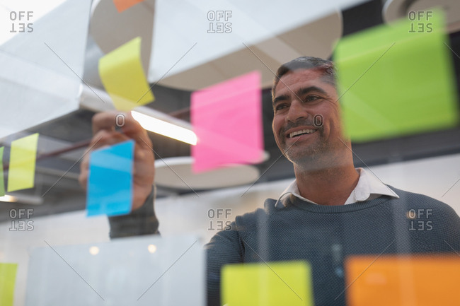 Businessman smiling while looking at sticky note