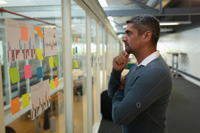 Thoughtful businessman looking over sticky notes in office