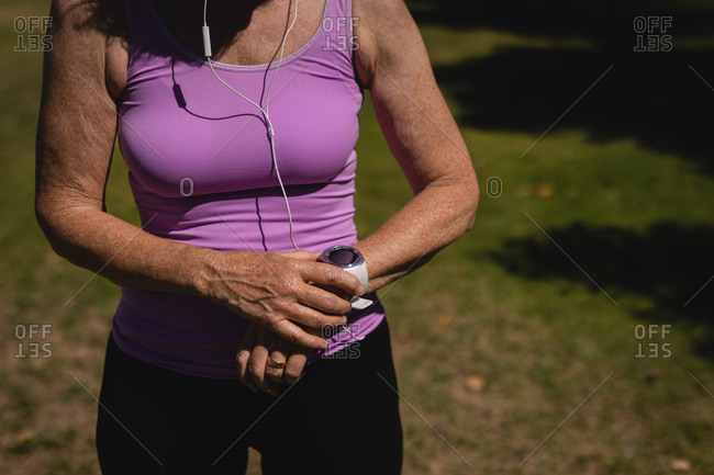 Active senior woman using smartwatch in the park