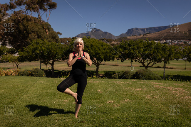 Active senior woman performing yoga in the park