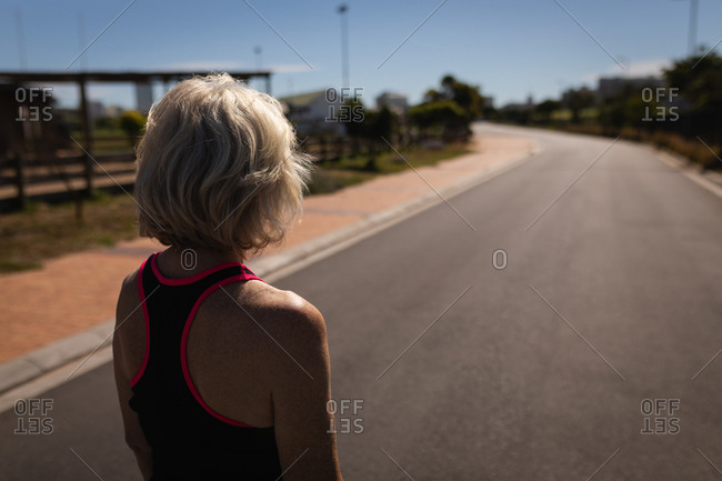 Active senior woman looking at road in the sunshine