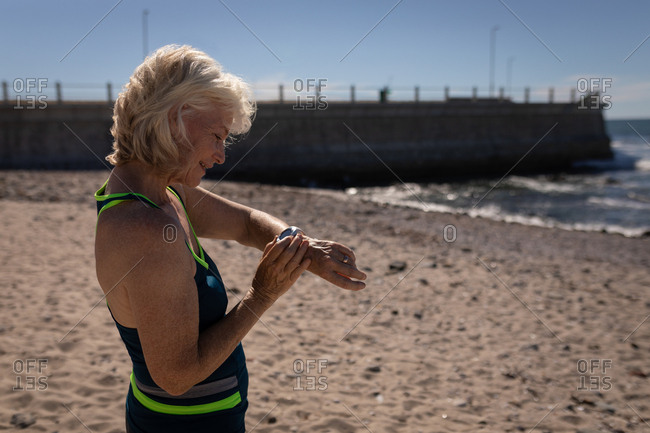 Active senior woman using smartwatch on the beach