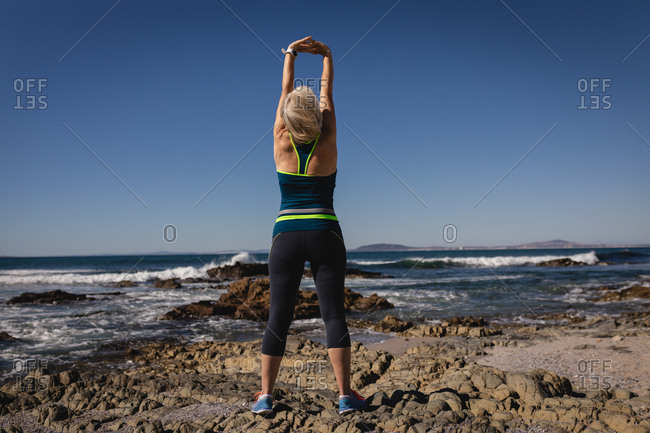 Active senior woman exercising on the beach in the sunshine