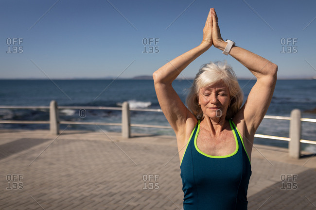 Active senior woman performing yoga on a promenade in the sunshine