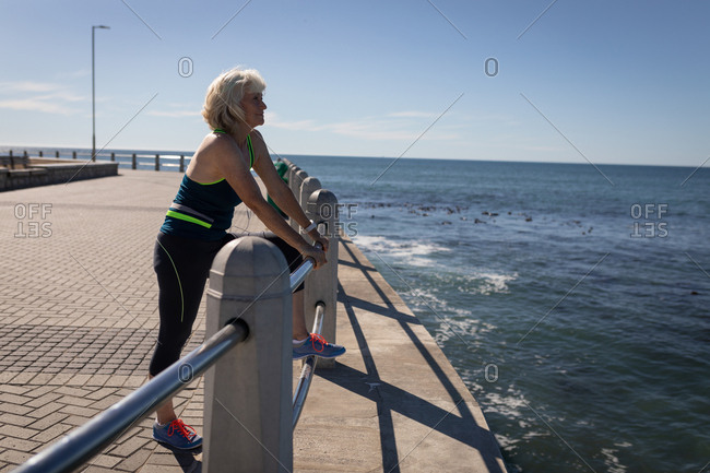 Active senior woman leaning on the guard rail of a promenade