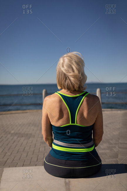 Active senior woman relaxing on a promenade in the sunshine