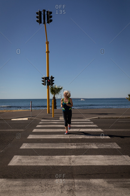 Active senior woman jogging on a road in the sunshine