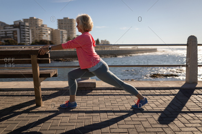 Active senior woman exercising on a promenade in the sunshine