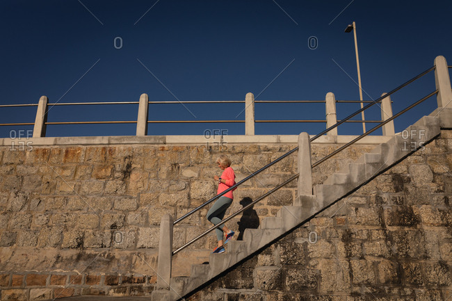 Active senior woman moving downstairs on a promenade