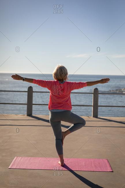 Active senior woman performing yoga on a promenade
