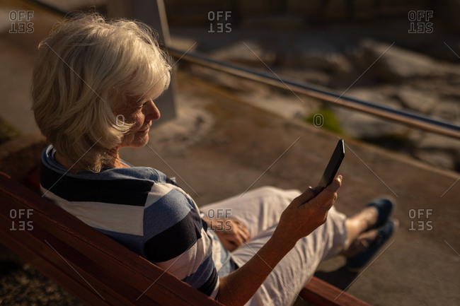 Active senior woman using mobile phone on a promenade