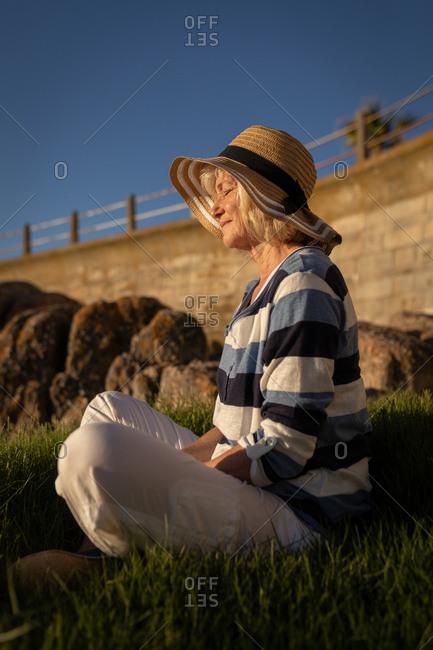 Active senior woman performing yoga on grass