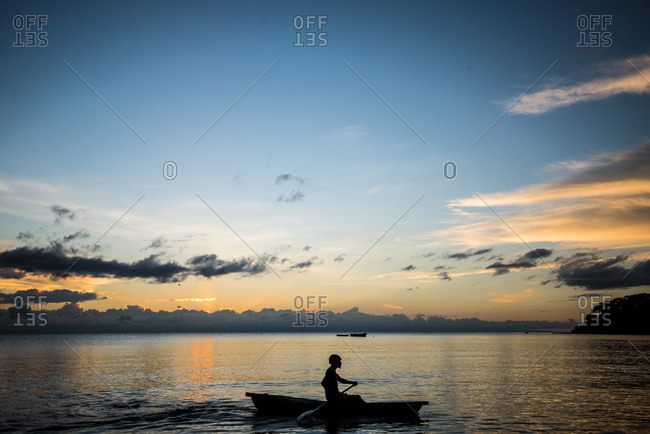 Silhouette of fishermen on a boat at sunrise, Malawi, Africa