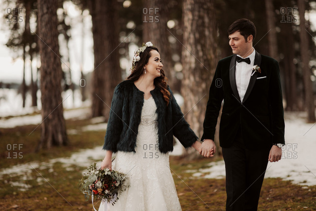 Bride and groom walking in forest hand in hand